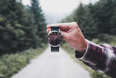 時計を手に持って見ている